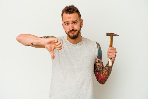 Giovane uomo caucasico tatuato isolato su sfondo bianco che mostra un gesto di avversione, pollice in giù. concetto di disaccordo.