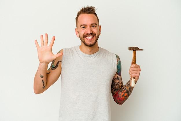 Giovane uomo caucasico tatuato isolato su sfondo bianco sorridente allegro che mostra il numero cinque con le dita.