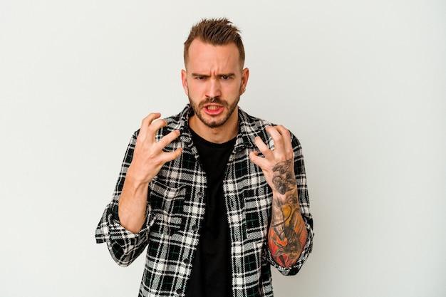 Giovane uomo caucasico tatuato isolato su sfondo bianco sconvolto urlando con le mani tese.