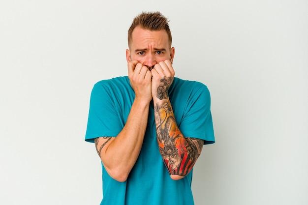 Giovane uomo caucasico tatuato isolato sulle unghie mordaci della parete bianca, nervoso e molto ansioso.