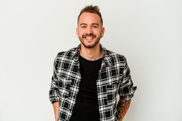 Giovane uomo caucasico tatuato isolato sul muro bianco felice, sorridente e allegro.