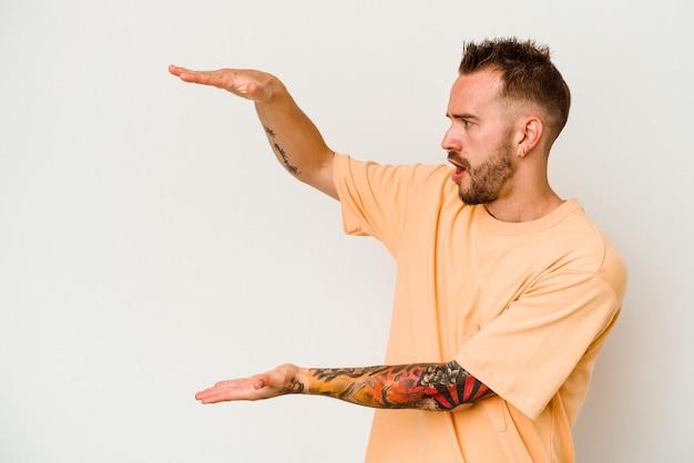 Giovane uomo caucasico tatuato isolato sul muro bianco scioccato e stupito in possesso di uno spazio di copia tra le mani.