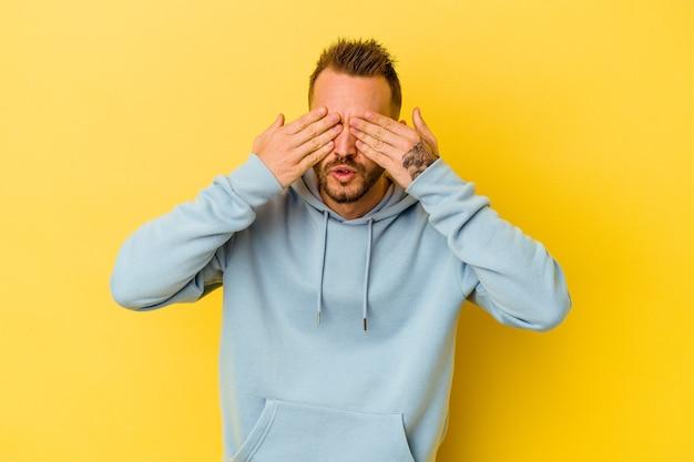 Giovane uomo caucasico tatuato isolato su sfondo giallo paura che copre gli occhi con le mani.