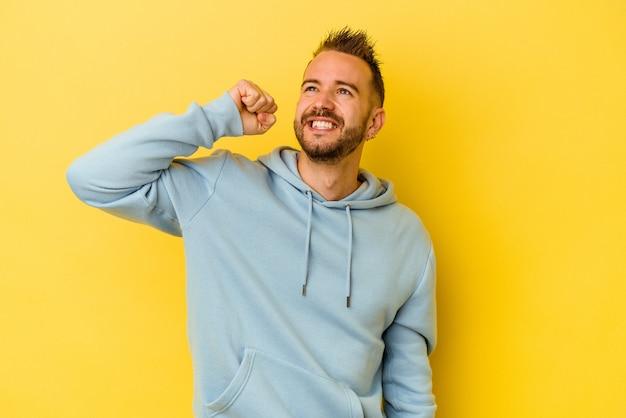 Giovane uomo caucasico tatuato isolato su sfondo giallo che celebra una vittoria, passione ed entusiasmo, felice espressione.