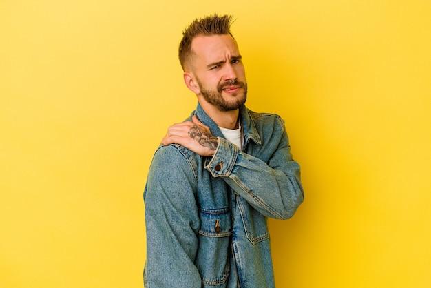 Giovane uomo caucasico tatuato isolato su sfondo giallo con un dolore alla spalla.