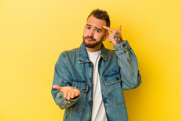 Giovane uomo caucasico tatuato isolato sulla parete gialla che tiene e mostra un prodotto a portata di mano.