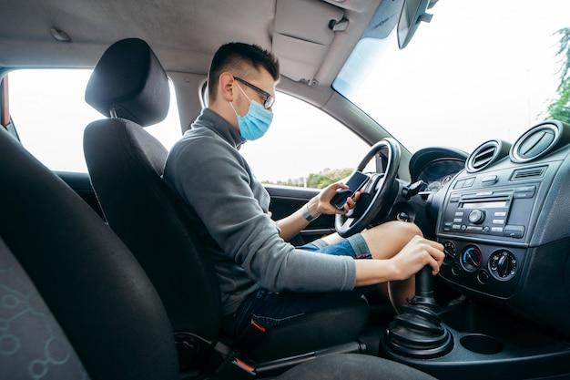 Giovane tassista in mascherina medica con uno smartphone in mano
