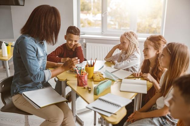 Giovane insegnante durante la lezione con gli alunni in aula