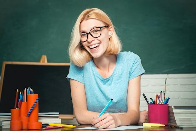 Giovane insegnante in bicchieri su sfondo verde lavagna