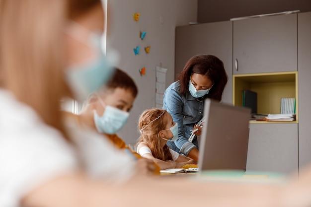 Giovane insegnante che aiuta la studentessa durante una lezione a scuola