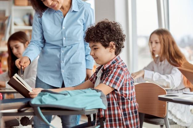 La giovane insegnante aiuta a leggere il suo studente. bambini delle scuole elementari seduti sulle scrivanie e leggere libri in classe.