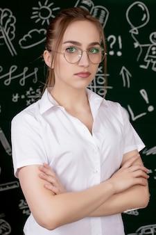 Il giovane insegnante è in piedi vicino alla lavagna in aula