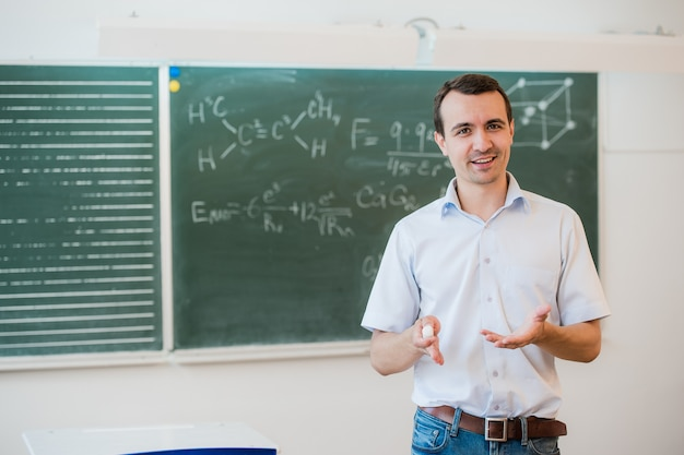 Giovane insegnante vicino alla lavagna nell'aula della scuola che comunica alla classe
