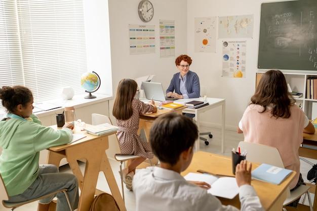 Giovane insegnante seduto sul posto di lavoro di fronte agli scolari