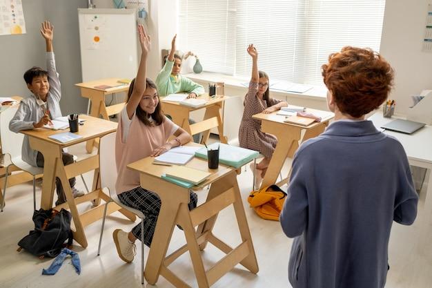 Giovane insegnante in piedi di fronte ai bambini che alzano la mano
