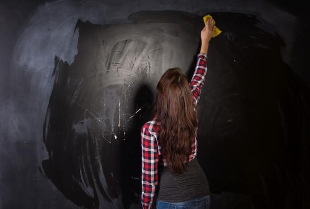 Giovane insegnante o studente che pulisce la lavagna raggiungendo con una spugna bagnata o uno spolverino mentre pulisce con la schiena alla telecamera