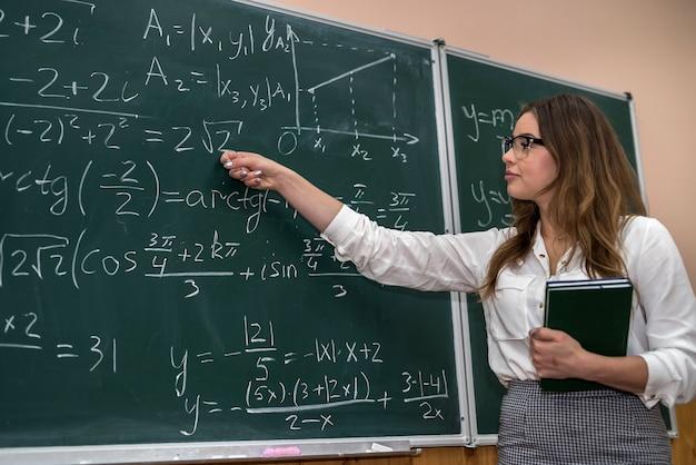 Giovane insegnante che scrive e spiega le formule matematiche su una lavagna. formazione scolastica