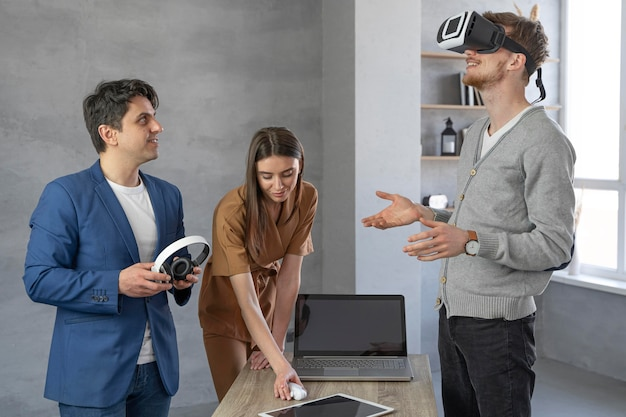 Giovane team di professionisti che lavorano con laptop e cuffie da realtà virtuale