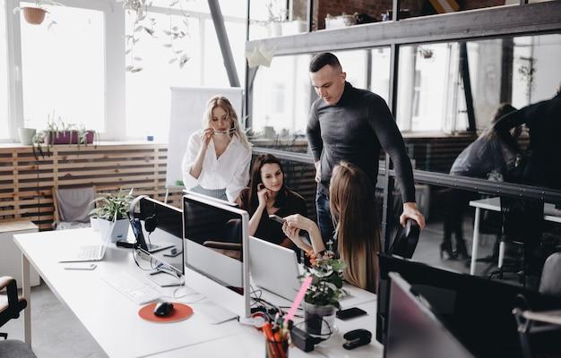 Il giovane team lavora alle scrivanie con un computer e laptop in un ufficio open space moderno e leggero