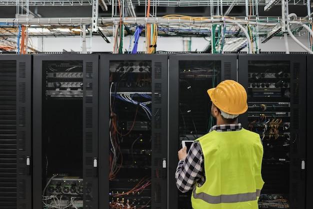 Uomo del giovane tecnico che lavora con il tablet all'interno di una grande sala del data center piena di server rack - focus sulla testa dell'uomo