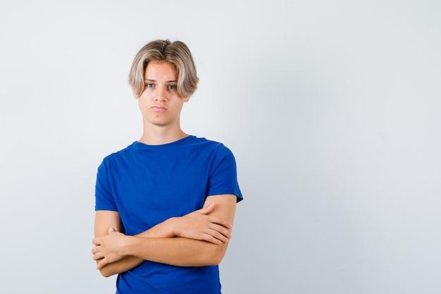 Giovane ragazzo adolescente in maglietta blu che tiene le braccia conserte e sembra dispiaciuto, vista frontale.