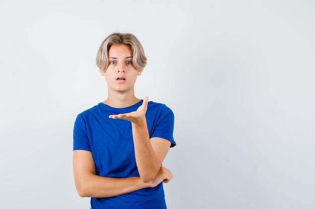 Giovane ragazzo adolescente in maglietta blu che allunga la mano davanti e sembra perplesso, vista frontale.