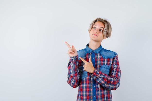 Giovane ragazzo adolescente in camicia a quadri che punta all'angolo in alto a sinistra, guardando in alto e guardando concentrato, vista frontale.