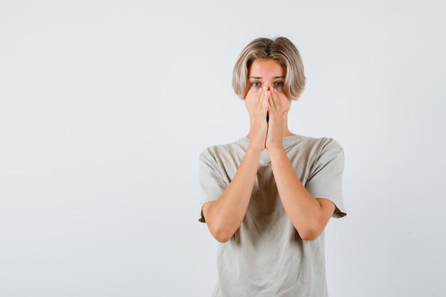 Giovane ragazzo adolescente che copre la bocca con le mani in maglietta e sembra agitato. vista frontale.
