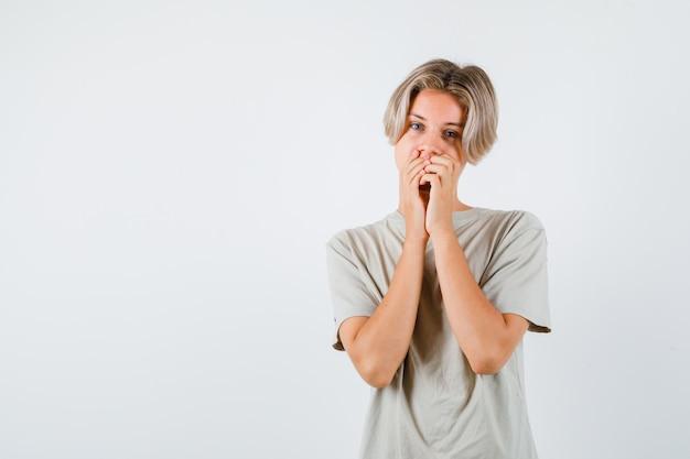 Giovane ragazzo adolescente che tiene le mani sulla bocca in maglietta e sembra sensato. vista frontale.