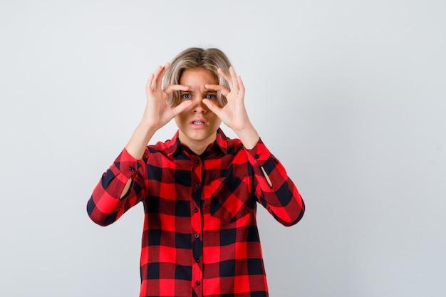 Giovane ragazzo adolescente guardando attraverso le dita in camicia a quadri e guardando focalizzato, vista frontale.