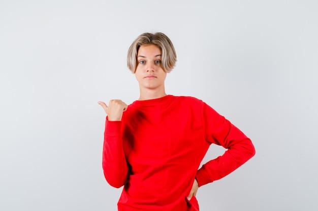 Giovane ragazzo adolescente che punta a sinistra con il pollice in maglione rosso e sembra indeciso, vista frontale.