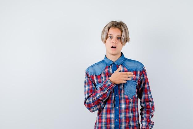 Giovane ragazzo adolescente che punta a destra con una camicia a quadri e sembra scioccato
