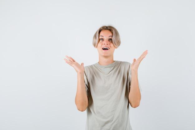 Giovane ragazzo adolescente che alza i palmi delle mani, alzando lo sguardo in maglietta e guardando felice, vista frontale.