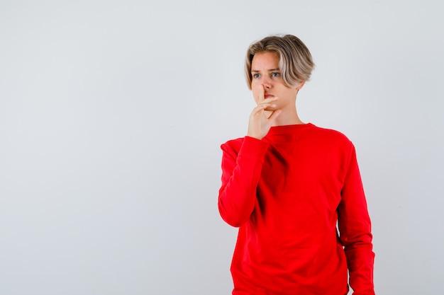 Giovane ragazzo adolescente che mostra gesto di silenzio in maglione rosso e sembra serio, vista frontale.