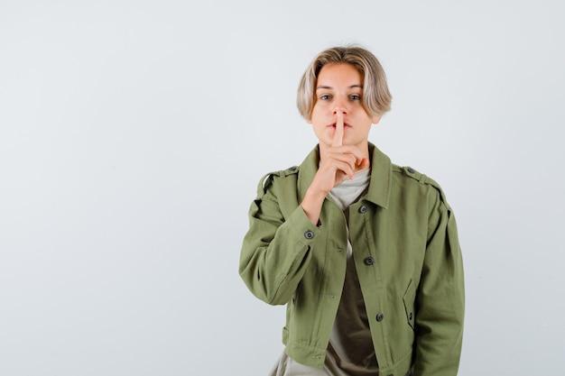 Giovane ragazzo teenager che mostra gesto di silenzio in maglietta e giacca, vista frontale.