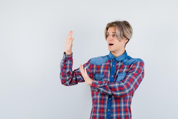 Giovane ragazzo adolescente che mostra il gesto di arresto in camicia a quadri e sembra spaventato, vista frontale.