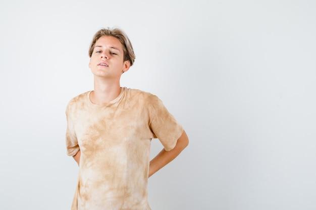 Giovane ragazzo adolescente che soffre di mal di schiena in maglietta e sembra stanco, vista frontale.