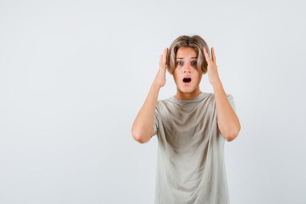 Giovane ragazzo adolescente in maglietta che tiene le mani sulla testa e sembra agitato