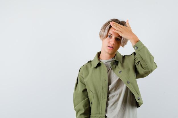 Giovane ragazzo adolescente con la mano sopra la testa in t-shirt, giacca e dall'aspetto fiducioso. vista frontale.
