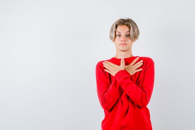 Giovane ragazzo adolescente con le mani sul petto in maglione rosso e guardando perplesso, vista frontale.