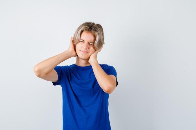 Giovane ragazzo adolescente con le mani sulle orecchie in maglietta blu e guardando annoiato, vista frontale.