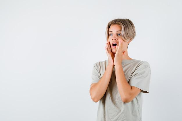 Giovane ragazzo adolescente con le mani vicino alla bocca