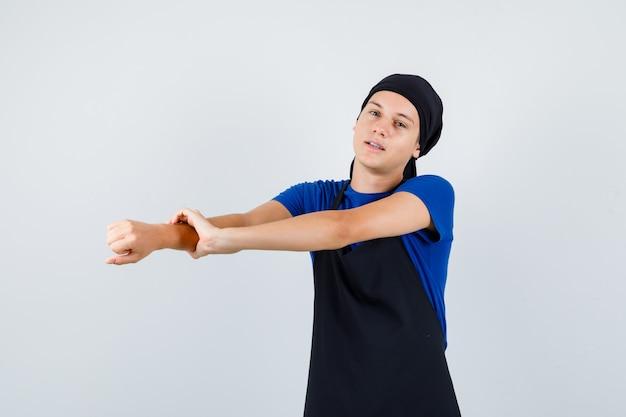 Giovane cuoco adolescente che allunga le braccia in maglietta, grembiule e sembra rilassato. vista frontale.