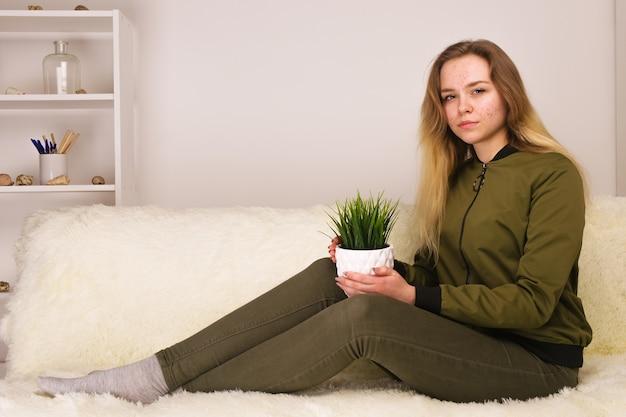 Giovane ragazza teenager con la faccia dell'acne che si siede sul sofà e che tiene la pianta d'appartamento verde