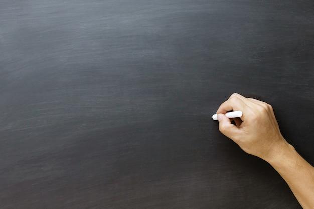Giovane mano teenager per disegnare e scrivere qualcosa sulla lavagna con il gesso. istruzione torna al concetto di scuola, lavagna.