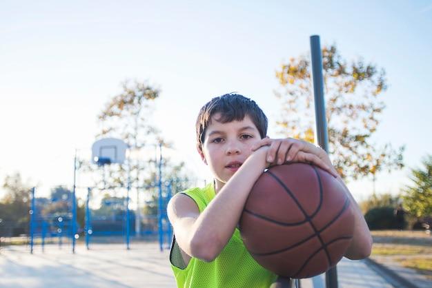 Giovane maschio adolescente con senza maniche in piedi su un campo da basket di strada mentre sorride alla telecamera