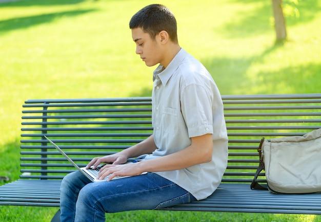 Giovane adolescente che utilizza il suo computer portatile nel parco