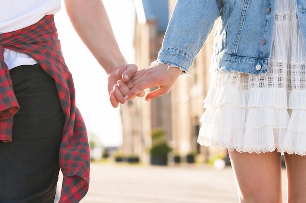 Giovani coppie adolescenti che si tengono per mano su una strada