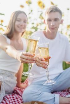 Giovane coppia di adolescenti picnic sul campo di girasoli al tramonto bevendo champagne