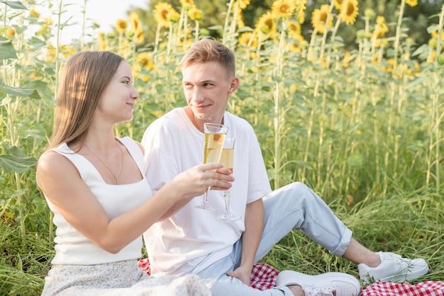 Picnic di giovani coppie adolescenti sul campo di girasoli nel tramonto. mangiando pizza e bevendo champagne